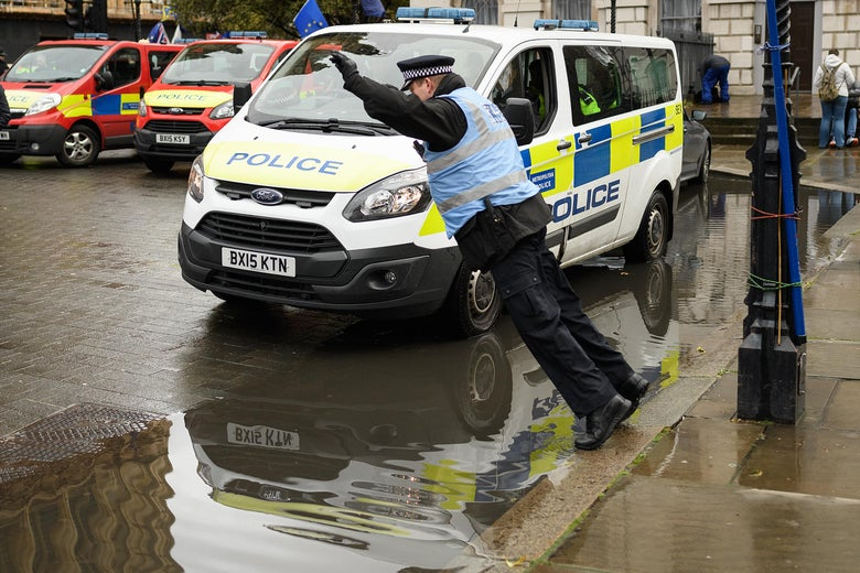 A police officer prepares to leap across a puddle as people take part in Brexit demonstrations outside the Houses of Parliament on March 12, 2019 in London, England.