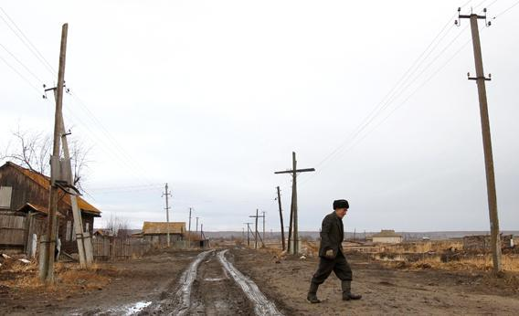 A man walks next to his old house in the village of Muslyumovo November 17, 2010. The village is located on the banks of the Techa river in Russia's Urals, one of the country's most lethal nuclear dumping grounds.