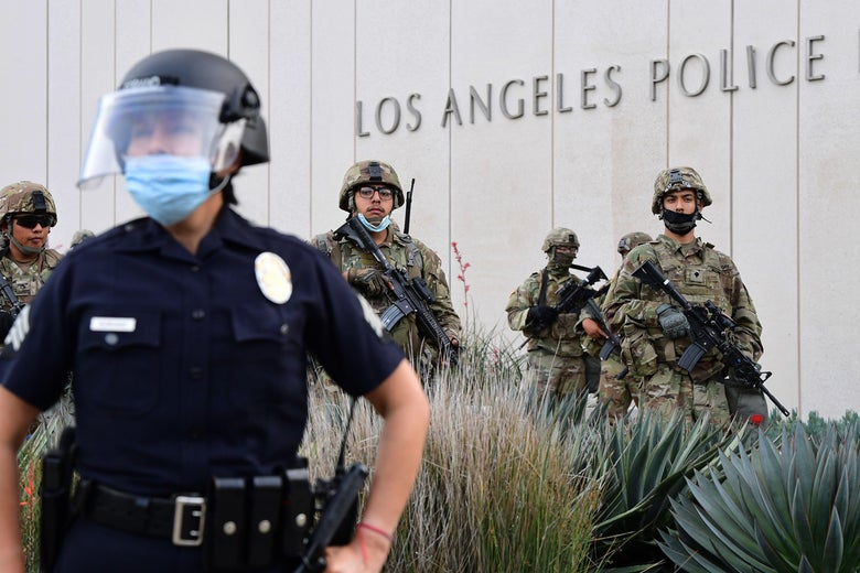 A police officer with a face shield stands with arms against his side in front of a building with the sign Los Angeles Police, along with National Guard members in camo and military gear.