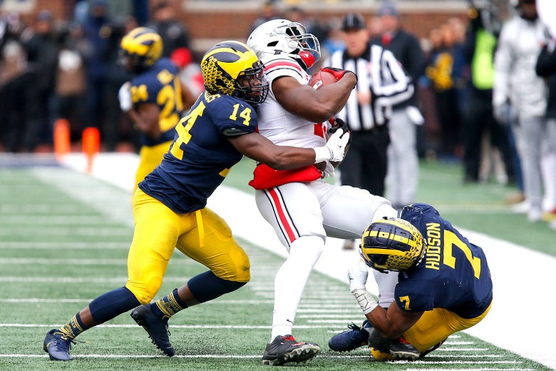 Josh Metellus tackles Rashod Berry around the waist while Khaleke Hudson goes for Berry's left leg. Berry is clutching the football.