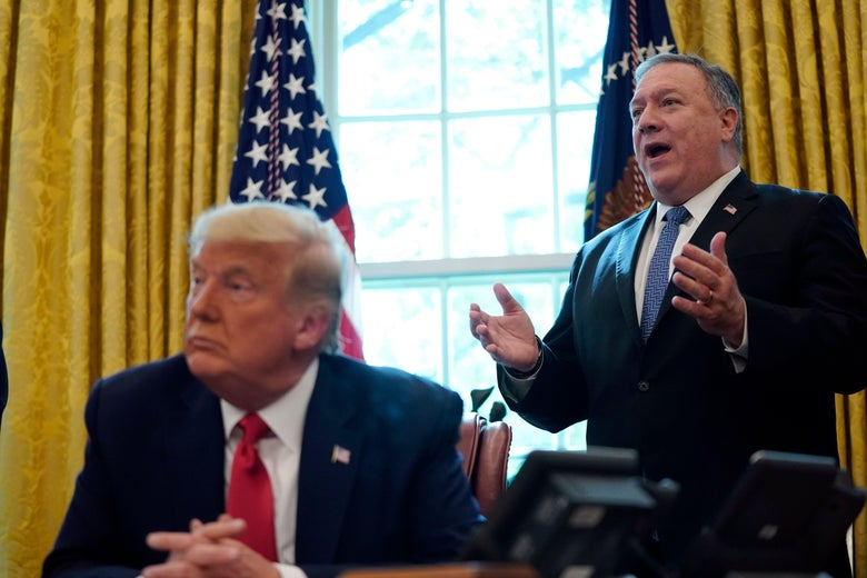 Mike Pompeo stands behind President Trump who's seated in the Oval Office.