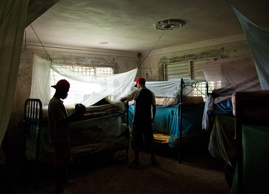 BOCA CHICA, DOMINICAN REPUBLIC. Players live in abandoned houses where they train all day with other prospects. Mosquito nets cover rotten mattresses in this training camp. Players hope to sign with a professional team after they turn 16.5.