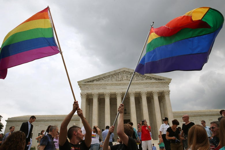 People wave rainbow flags outside the Supreme Court.