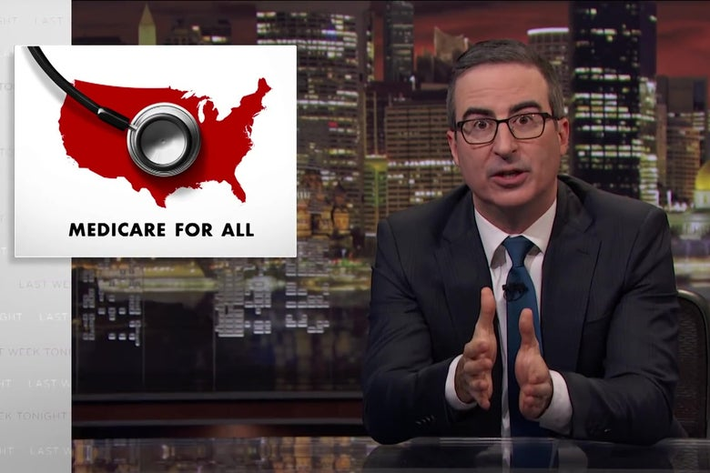 "John Oliver sits at an anchorperson's desk, in front of an image reading ""Medicare For All."""