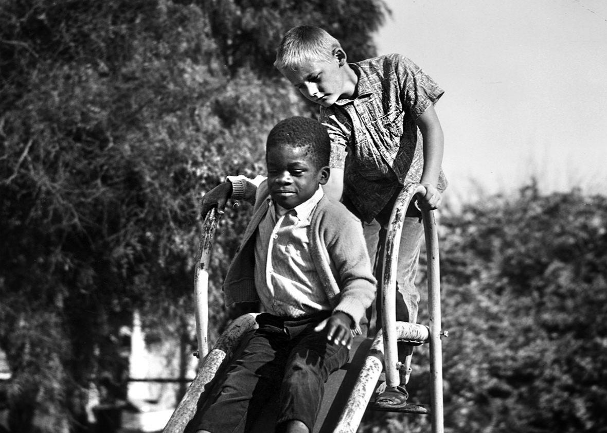 An African-American boy sits at the top of a playground slide, a