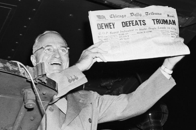 "Historic black-and-white photo of Truman holding a newspaper with the headline ""Dewey Defeats Truman"" up  for the camera."