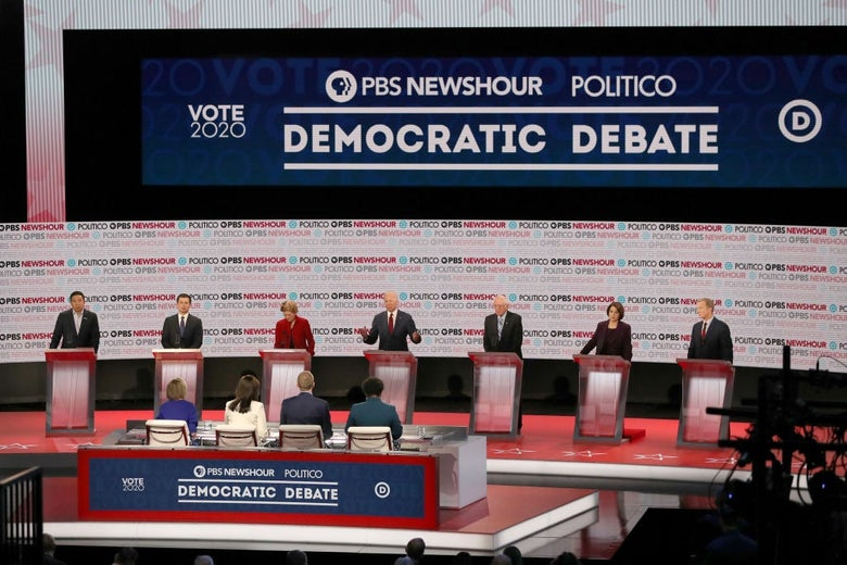 Seven candidates and four moderators pictured from an elevated position.