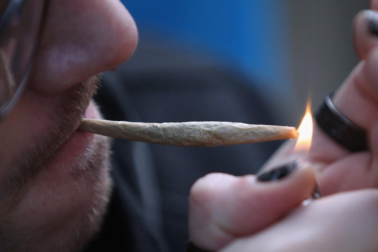 A close-up photo of a face with a joint between the lips and hands holding a lighter to light it.