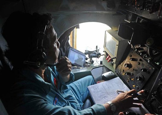 A crew member looks out the window of a search aircraft during search operations for missing Malaysia Airlines flight 370 over the southern seas off Vietnam on March 9, 2014.