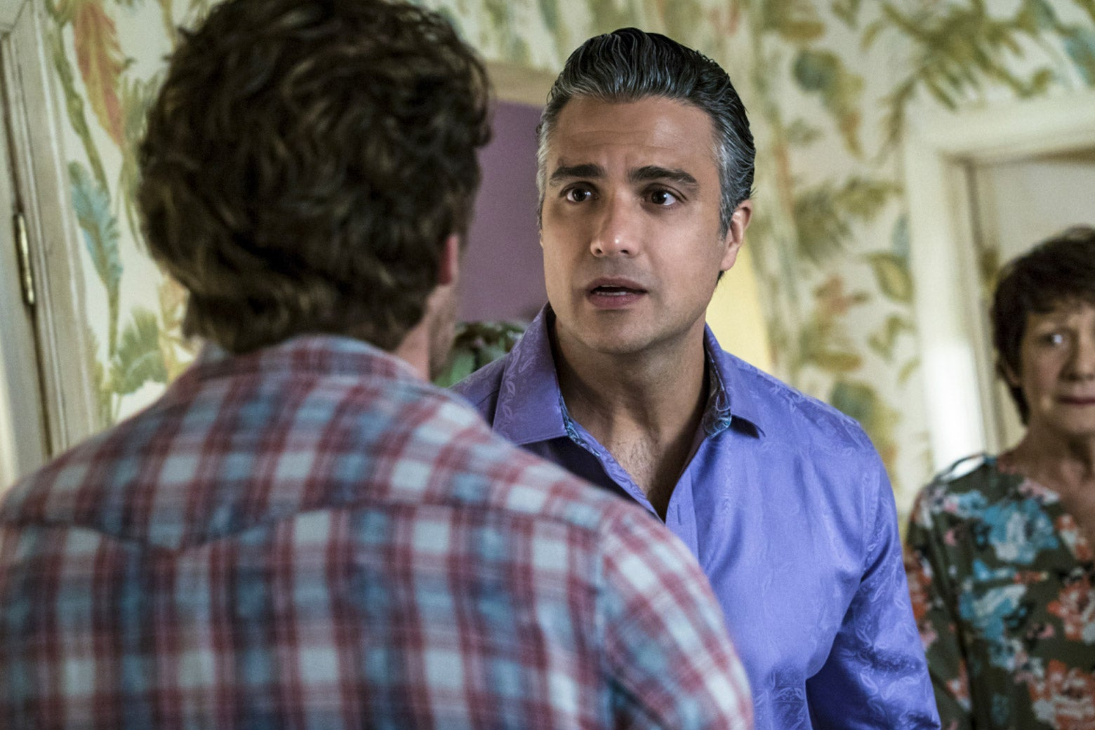 In a still from Jane the Virgin, Rogelio and Alba look upset, facing Jason.