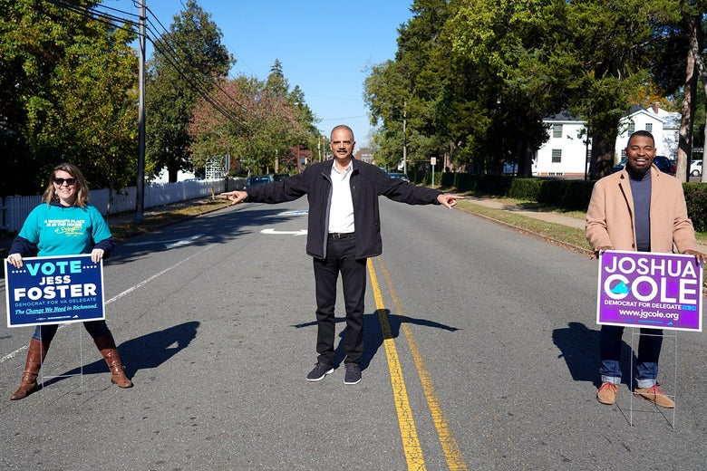 Eric Holder stands in the middle of the road and points at Jess Foster and Joshua Cole, who hold campaign yard signs.