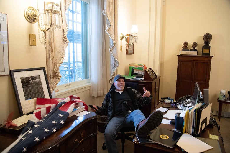 A man in a baseball cap sits with his left foot up on Speaker of the House Nancy Pelosi's desk.