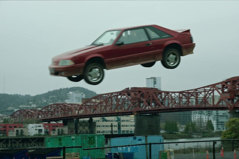 A 1980s Ford Mustang suspended in mid-air after being driven off a ramp.