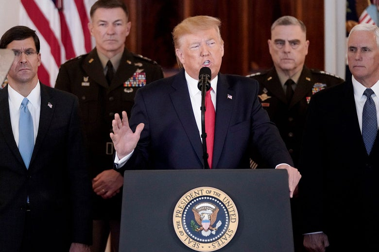 Donald Trump stands at a White House lectern, speaking and raising his hand, as the Joint Chiefs of Staff stand in the background.