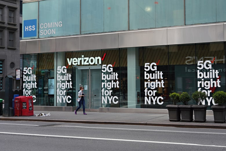 "A person walks by a Verizon storefront with signs that say ""5G built right for NYC."""