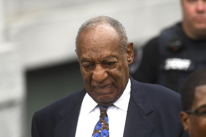 Bill Cosby, dressed in a suit, looks downward
