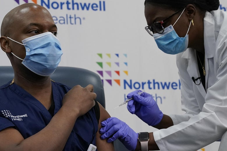 A Black man in navy scrubs and a surgical mask rolls up his sleeve as another health care worker gives him a vaccine.
