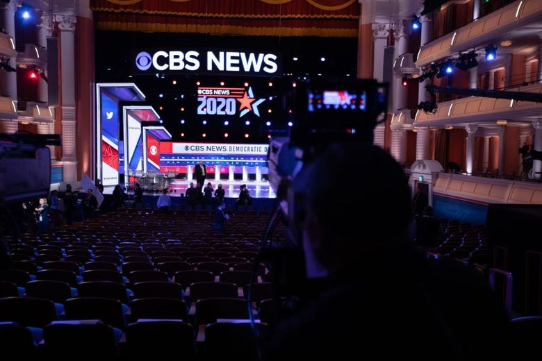 A cameraman trains across empty seats and onto the stage, where a red, white, and blue CBS News backdrop has been set up.