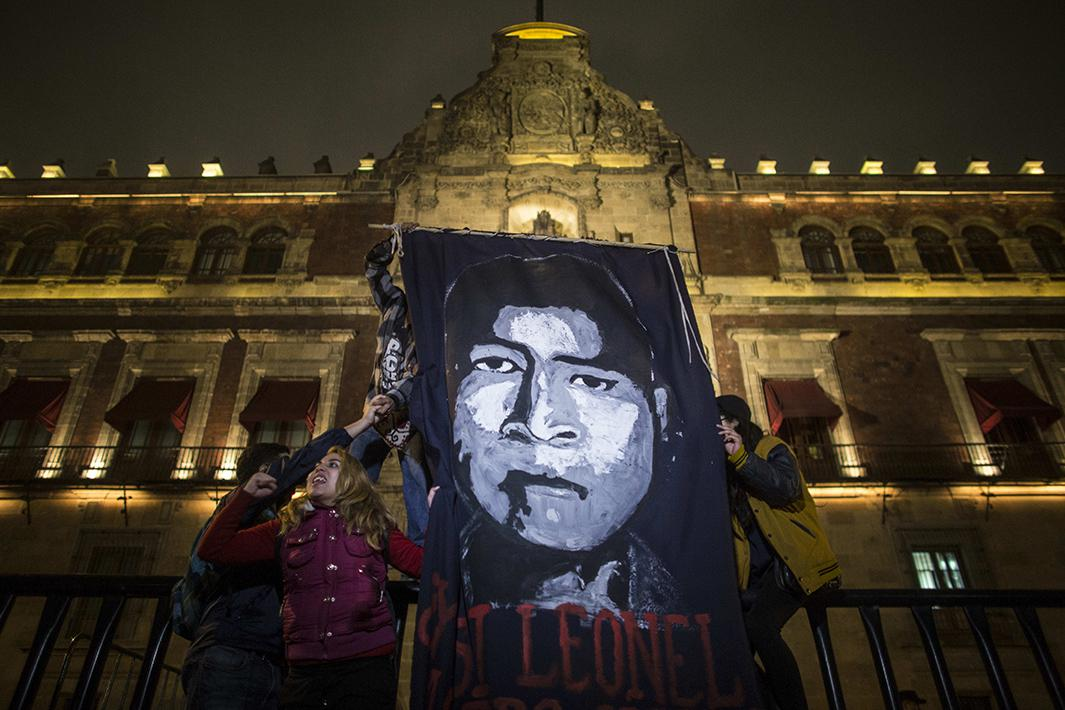 Demonstrators hold a sign with the face of one of the missing students during a spontaneous demonstration on November 8.