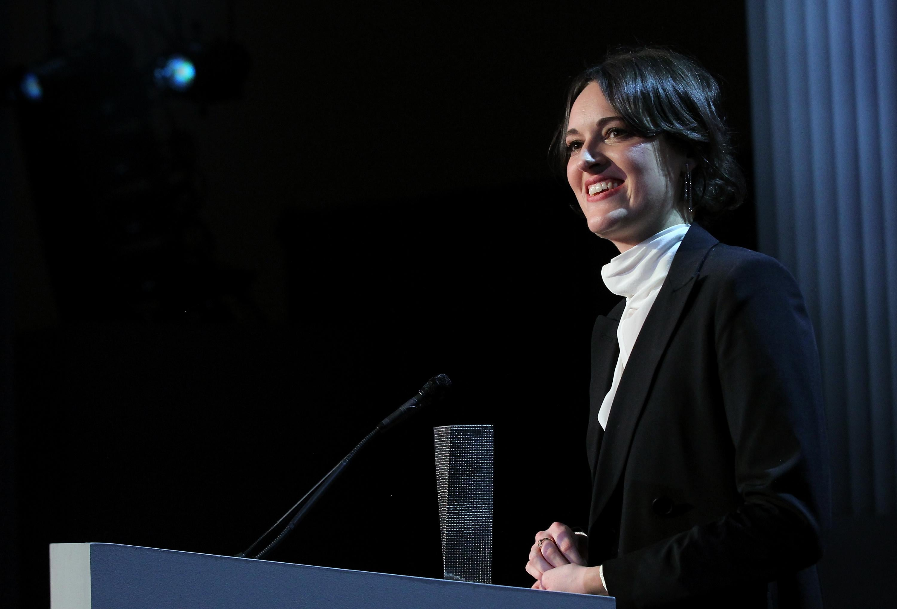 Phoebe Waller-Bridge stands at a podium in a dimly lit room.