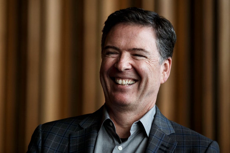 Comey, dressed in a sport coat against a backdrop of brown curtains, laughs.