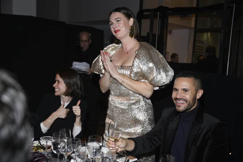 """Alison Roman, in a platinum dress with puffy sleeves, stands at a dinner table smiling with her hands clasped together as she attends """"The Bloomberg 50"""" Celebration at The Morgan Library on Dec. 9, 2019 in New York City."""