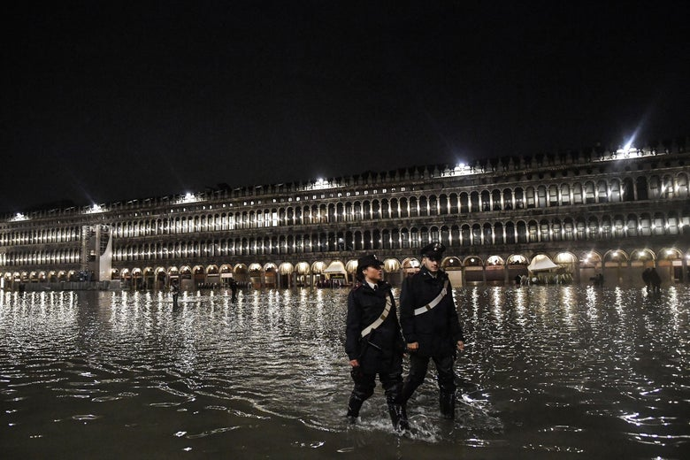 Police patrol across the flooded St. Mark's Square.