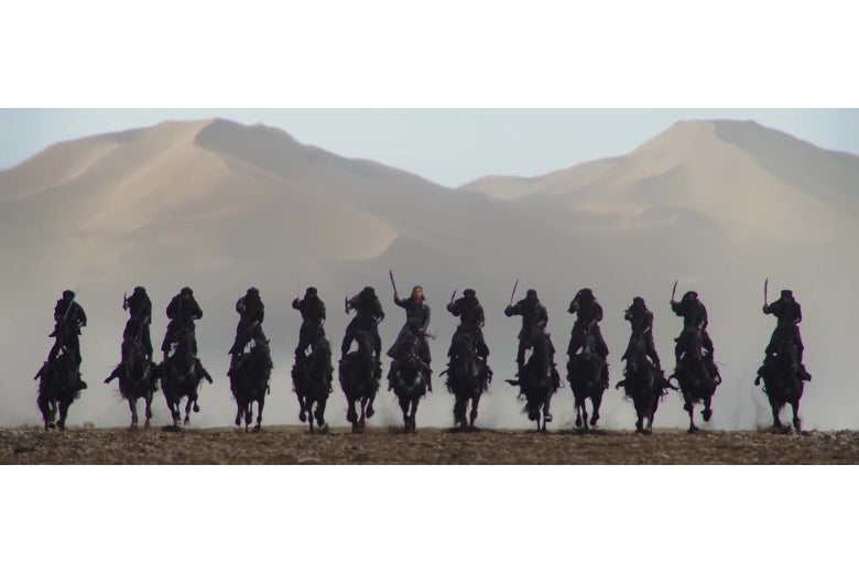 13 soldiers on horseback, riding in a row straight at the camera, in a still from Mulan.