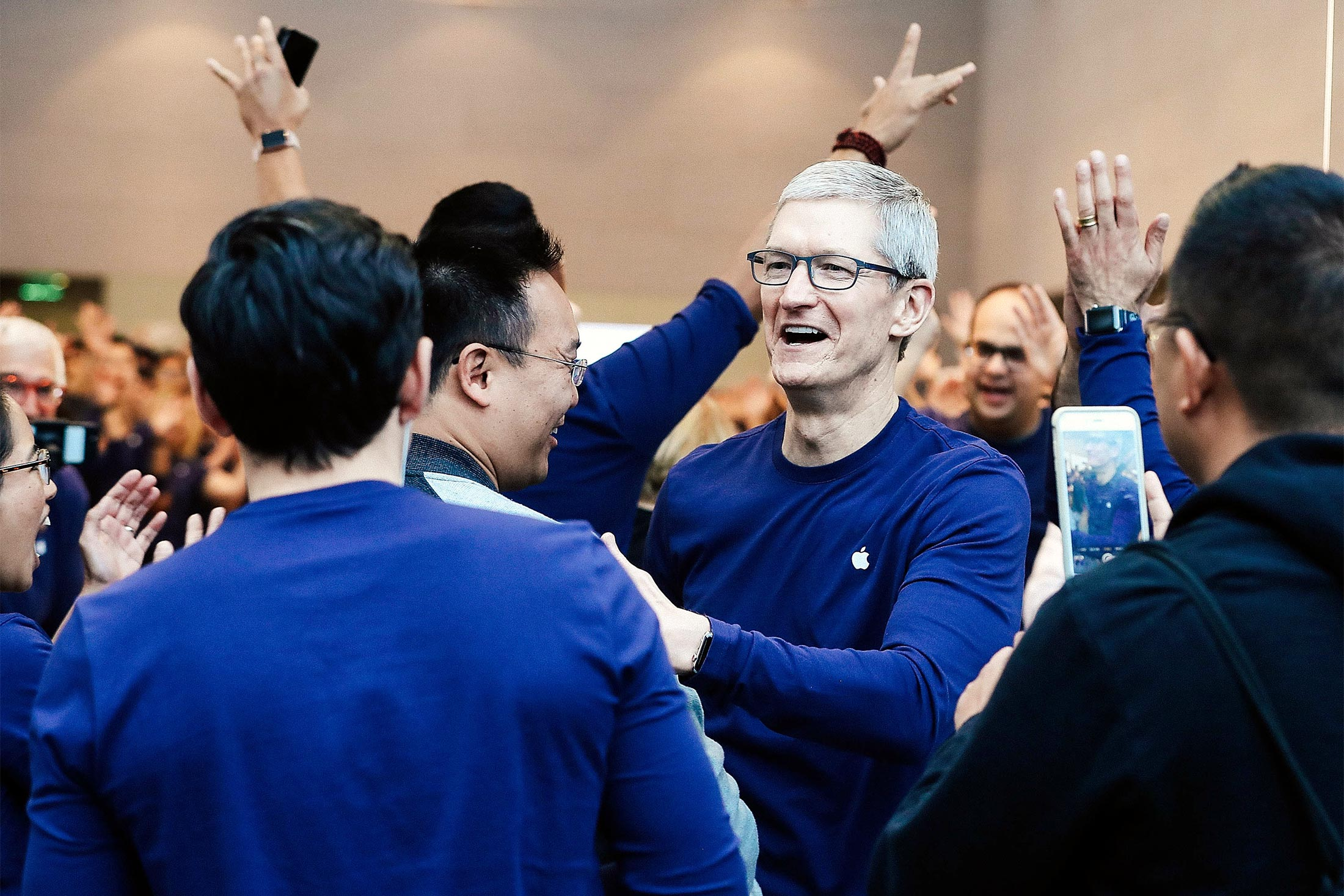 Tim Cook wears a long-sleeved Apple T-shirt as he greets customers for the iPhone X release at an Apple Store.