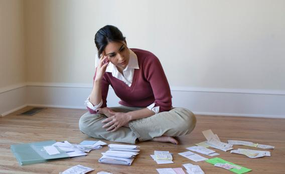 Woman sits in front of bills and receipts.