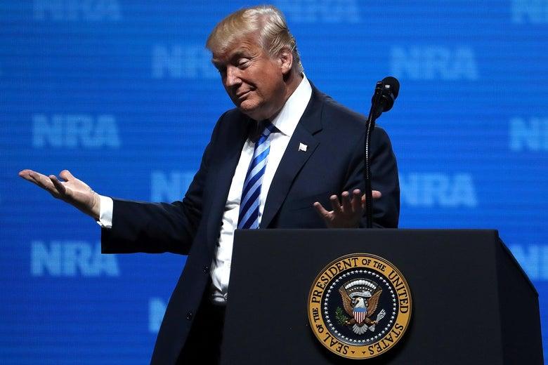 Trump shrugging at a podium.