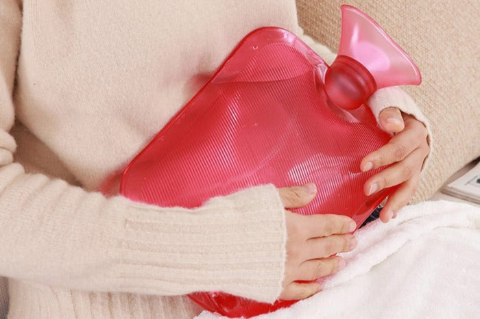 Woman holding the Attmu Classic Rubber Transparent Hot Water Bottle 2 Liter With Knit Cover to her stomach.