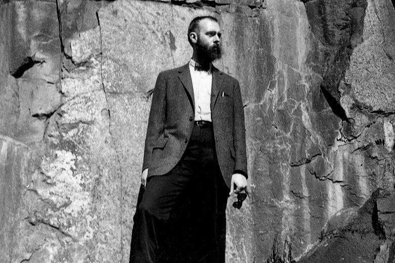 Gorey standing beside a cliff face.