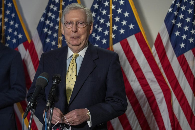 Mitch McConnell stands behind a microphone and in front of American flags while holding a face mask.