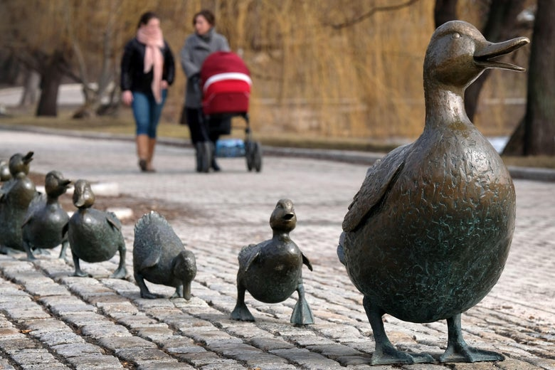 Women push a pram past a sculpture of a duck and ducklings on a sunny spring day in Moscow.