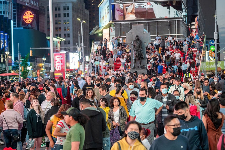 Large crowds of people with and without masks fill Times Square.