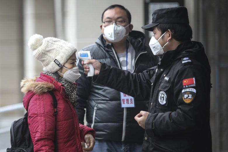 A security personnel on the right checks the temperature of a woman on the left. All 3 people in the photo are wearing flu masks.