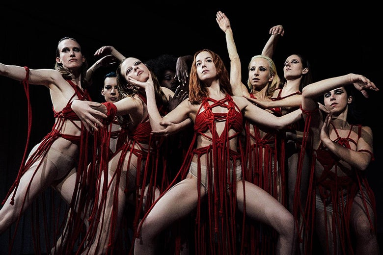 Dancers in red string outfits.