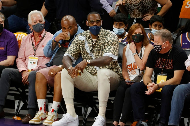 James, wearing a mask over his mouth but not his nose, looks toward the court from a front-row seat.