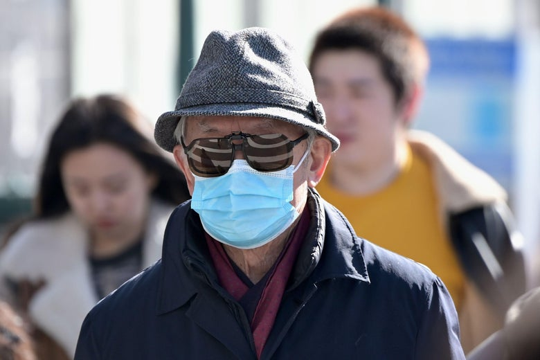 Man wearing a surgical mask and sunglasses, walking outside.