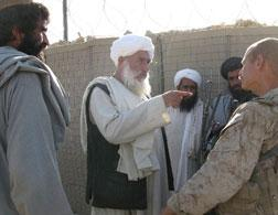 An Afghan discusses a battle damage claim with Marine Lt. Mike Kuiper. Click image to expand.