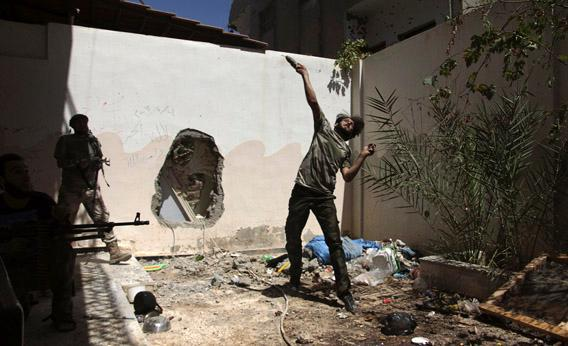 A Free Syrian Army fighter throws a homemade bomb towards forces loyal to Syria's President Bashar al-Assad as fellow fighters watch in Deir al-Zor July 14, 2013.