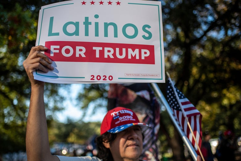 """A man holds up a """"Latinos for Trump"""" sign."""