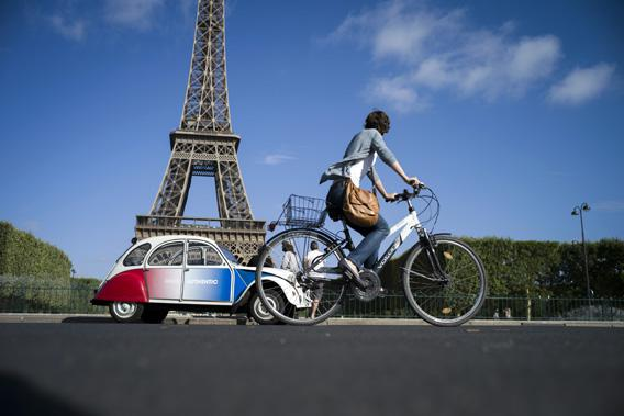 A cyclist rides past a French Citroen 2CV parked in front of the famous Eiffel Tower in Paris on August 3, 2012.