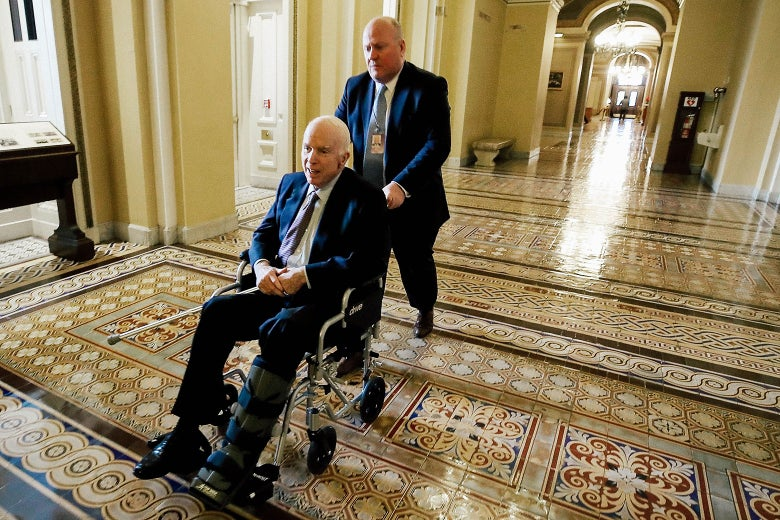 Arizona Sen. John McCain is pushed in a wheelchair between votes on Capitol Hill on Nov. 30 in Washington.