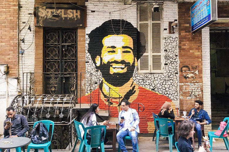 People sit at a café in downtown Cairo with a mural depicting Mohamed Salah in the background on April 4.