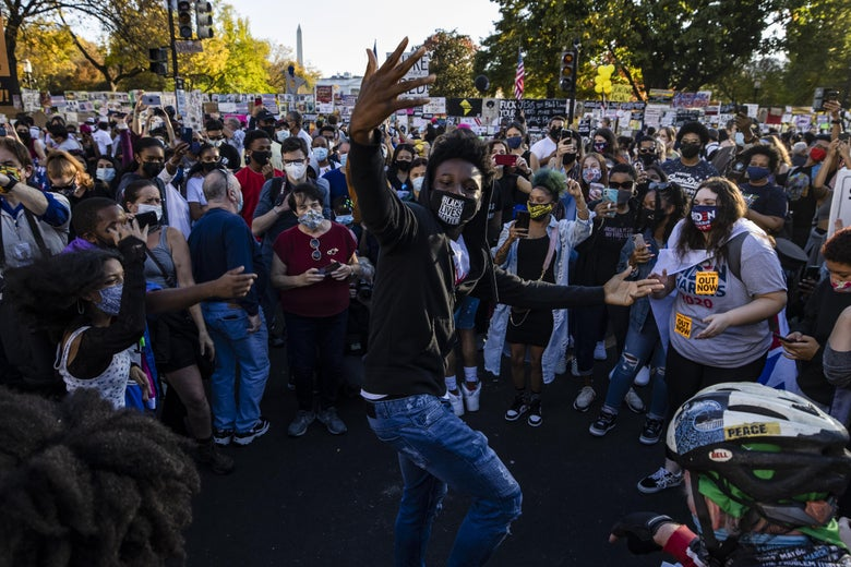 A young person dances, surrounded by other people on a street. All are wearing face masks, some are holding signs.