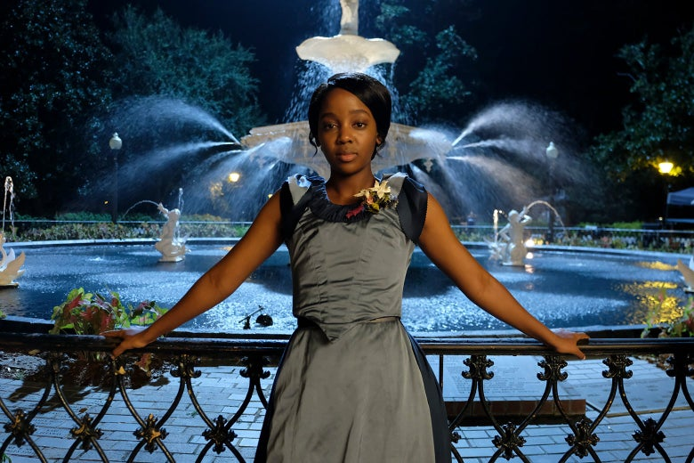 A woman in a blue dress leans against a railing in front of a fountain in a still from The Underground Railroad.