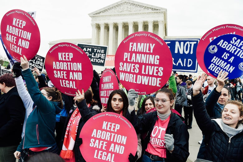 """Protesters hold up signs that say things like """"Keep abortion safe and legal"""" and """"Safe abortion is a human right."""""""
