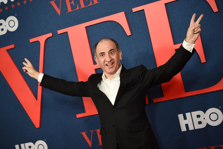 Armando Iannucci, making the Nixon victory gesture, on a red carpet.